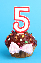 Birthday cupcake with chocolate frosting on blue background
