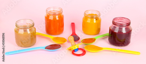 Baby puree in spoons with nipple on pink background