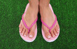 Beautiful woman legs in summer slippers on green grass