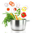Fresh vegetables falling into a stainless steel casserole pot