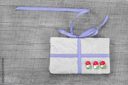 Liebevoll verpacktes Geschenk auf Holz für den Glückspilz