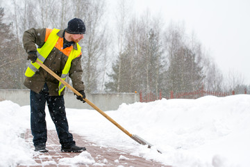 Man worker in uniform shoveling snow