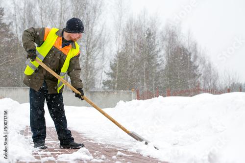 Man worker in uniform shoveling snow - 50071746