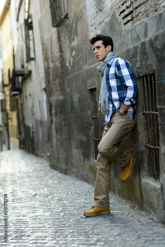 Handsome man with modern hairstyle in urban background