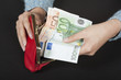 Woman's hands holding red purse and Euro banknotes