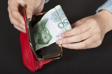 Woman handling a Chinese 50 Yuan banknote in a red purse