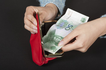 Woman holding a Chinese 50 Yuan banknote in a red purse