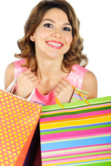 Young cheerful girl with colorful shopping bags isolated