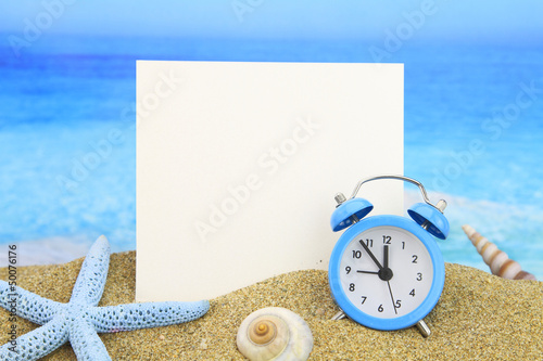 Summer time. Paper card and alarm clock on the beach