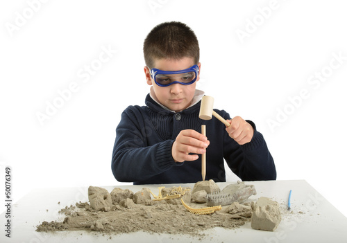 Child archaeologist excavating for dinosaur fossil