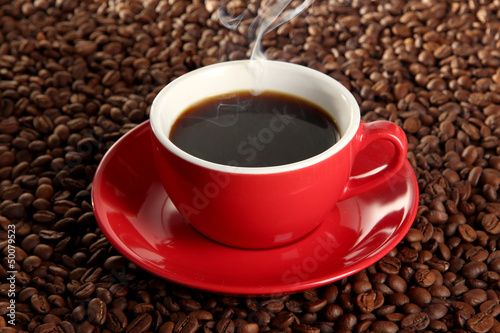 Cup of coffee on coffee beans background