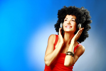 Beautiful smiling woman with afro hair and with headphones