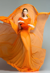 beautiful woman in long orange dress posing in the studio
