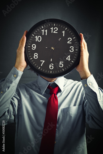 Businessman with black clock, deadline concept