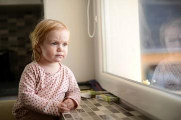 la jeune fille regarde par la fenêtre