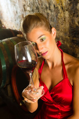 Woman looking at wine glass in the cellar