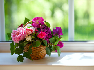 colorful roses in a basket on window-sill