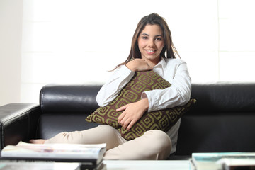 Beautiful teenager on a couch at home embracing a cushion