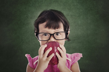 Female preschooler eats red apple