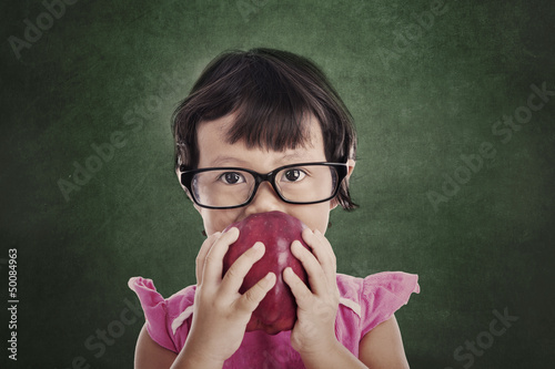 Female preschooler eats red apple