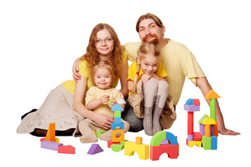Happy redhead father, mother and two children building from toy