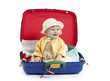 baby girl seated in a suitcase on white
