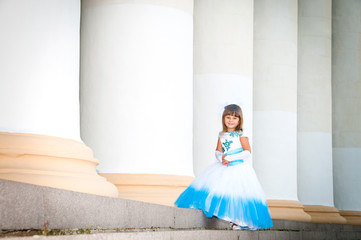 Little bride. A girl in a lush white and blue wedding dress