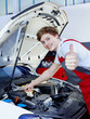 Satisfied car mechanic shows thumb up for a good job