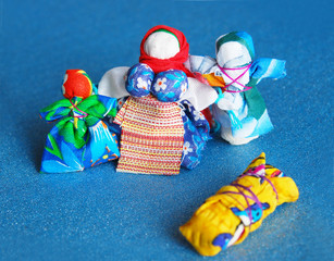 Hand-made colorful dolls on blue background