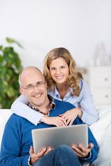 lächelndes paar zu hause mit laptop