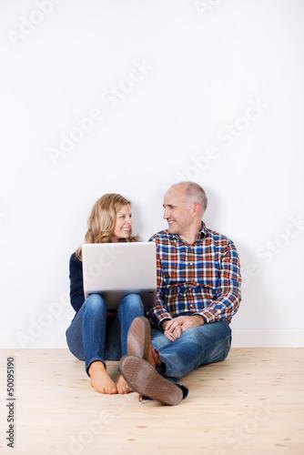 paar sitzt mit laptop in einem leeren zimmer