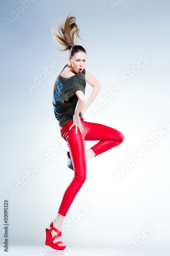 sexy model with slim body dressed in red jumping and screaming