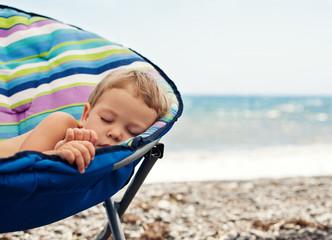 baby boy sleeping on the beach