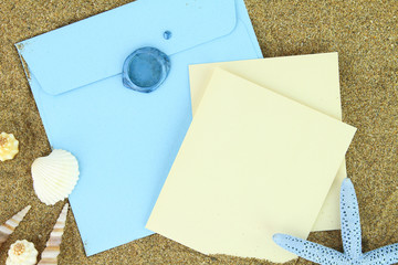 Paper card and blue envelope on the beach