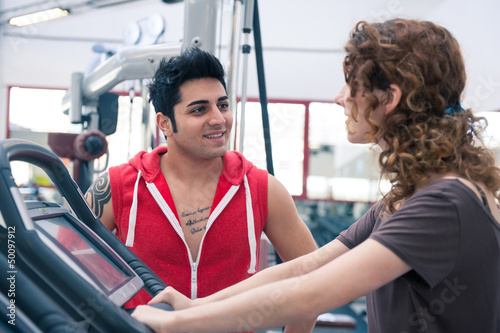 Couple talking at the gym while training.