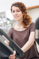 Young woman training in the gym with bike.