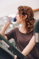 Young woman having a rest drinking a beverage in the gym.