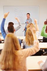 Studenten heben Hände im Unterricht