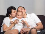 mom and dad kiss baby