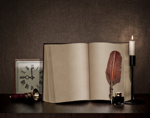 vintage book, pen, watch and candle