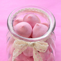 Pink marshmallow in glass jar on pink background