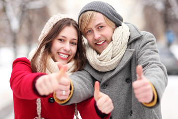 Winter couple with thumbs up