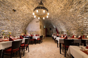 romantic arch stonewall in knight room with tables and candlelit