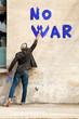 man writes on a wall no war