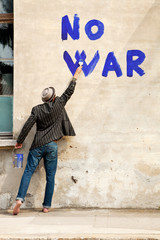man writes on a wall no war
