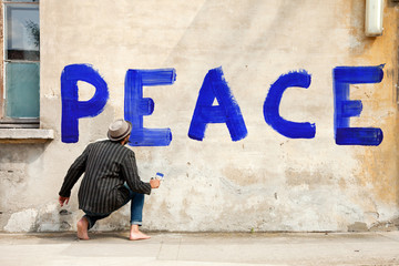 man writes on a wall for the peace in the world