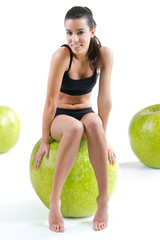 woman in fitness clothes sitting atop a giant apple