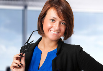 Young businesswoman holding her glasses