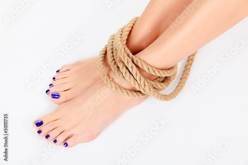Female legs with thick rope round them