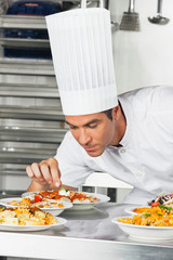 Male Chef Garnishing Pasta Dishes